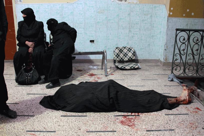 W prowizorycznym szpitalu kobiety czekają na pomoc obok zwłok ofiary ataku lotniczego w Douma /AFP
