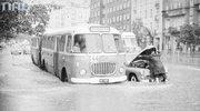 Widok ulicy Puławskiej w kierunku placu Unii Lubelskiej. Na pierwszym planie widoczna zepsuta taksówka osobowa marki Warszawa oraz mijający ją autobus Jelcz linii 144, 1968.