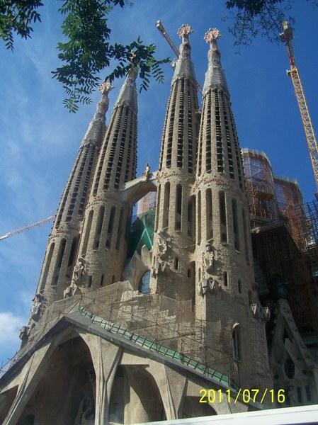 HISZPANIA - Sagrada Familia w Barcelonie (zdj. z roku 2011 ) - secesyjny kościół w Barcelonie w Katalonii o statusie bazyliki mniejszej, uważany za główne osiągnięcie projektanta Antoniego Gaudíego. Budowa bazyliki Sagrada Familia zaczęła się w... 1882 roku. W założeniu architekta sama konstrukcja budowli miała przypominać wielki organizm. Antoni Gaudi, który przejął kontrolę nad całym przedsięwzięciem w 1883 roku, pracował nad nim, aż do swojej tragicznej śmierci w 1926 roku, przy czym poświęcił mu całkowicie ostatnie 15 lat swojego życia.  Po jego śmierci prace nad projektem przejęła grupa architektów, która na podstawie planów Gaudiego chciała dokończyć budowę. Jednak w wyniku wybuchu wojny domowej w Hiszpanii, podczas której część dokumentów zaginęła bądź została zniszczona, ich praca została znacznie utrudniona.  Jak przewidują eksperci, budowa bazyliki może zostać ukończona całkowicie za około 17 lat. Gdyby tak się się stało, całość realizacji przedsięwzięcia zamknęłaby się w okresie... 146 lat.