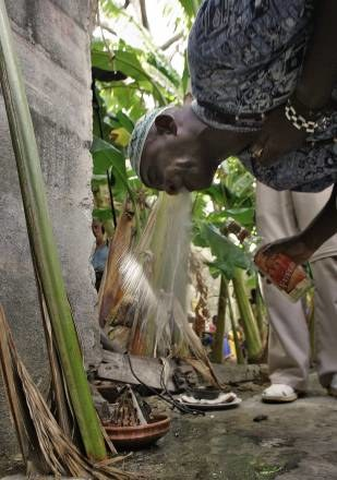 Wyznawca Santerii składa rum w ofierze Orisha /AFP