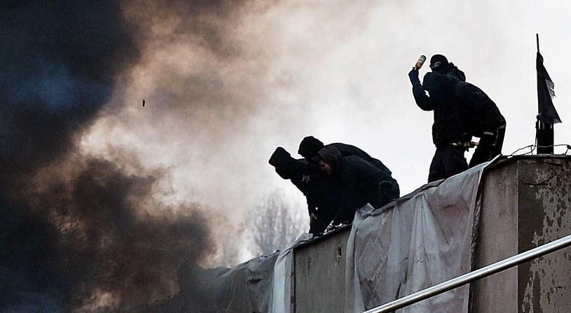 Z dachu skłotu rzucano butelkami i kostkami bruku /AFP