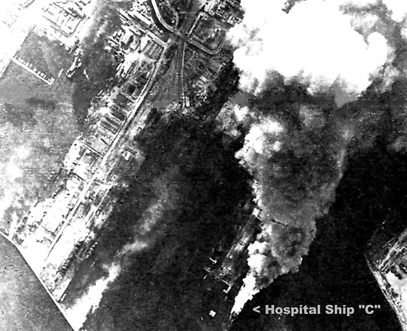 """Zdjęcie płonącego """"Stuttgartu"""" wykonane z pokładu amerykańskiego bombowca.  Fotografia lotnicza pokazuje fragment bazy Kriegsmarine w porcie gdyńskim, tuż po  nalocie samolotów amerykańskich /Odkrywca"""