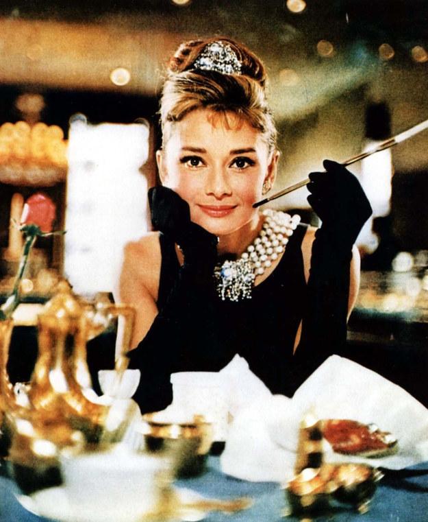 """Zdjęcie z filmu """"Śniadanie u Tiffany'ego"""", w którym delikatnie trzyma przy ustach długą, szklaną fifkę, rozpala zmysły i wyobraźnię. /EastNews /East News"""