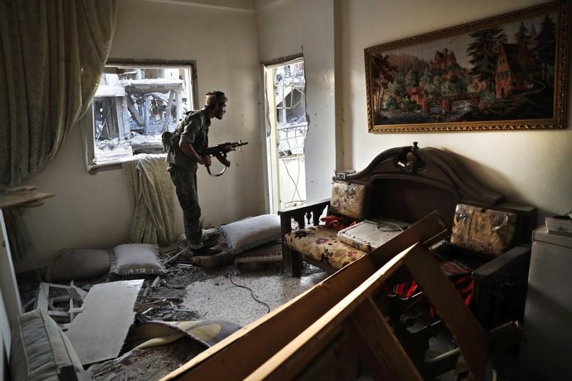 Żołnierz Syryjskich Sił Demokratycznych (SDF) w zniszczonym mieszkaniu na linii frontu w Ar-Rakce w Syrii /AP Photo/Hussein Malla /East News