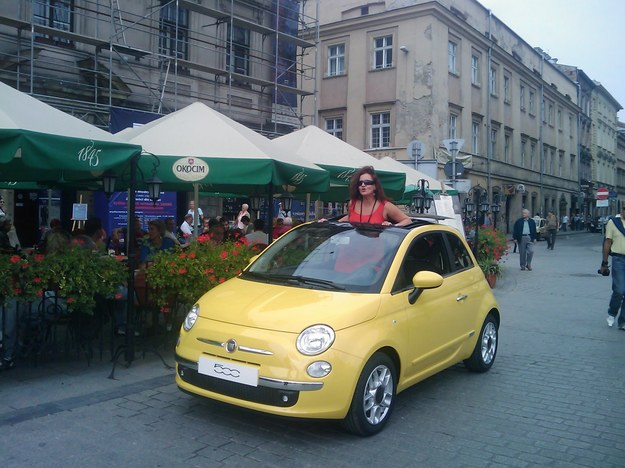 Fantastyczny Kraków, Rynek Główny, fiat 500, żółty, i kobieta w czerwonym DK72