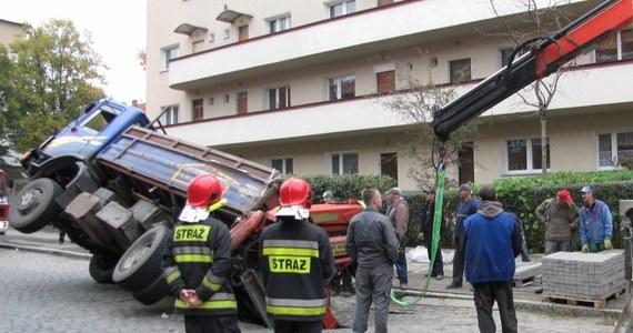 W Szczecinie zapadła się jezdnia pod ciężarówką wiozącą kostkę brukową. Auto częściowo wpadło w dziurę w ulicy Janickiego, a częściowo przewróciło na stojącego obok opla. Nikt nie został ranny, ale ulica jest całkowicie zablokowana. Służby czekają na dźwig. Odblokowywanie przejazdu może zająć nawet kilka godzin.