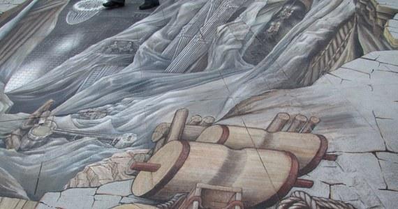 """Wielicki """"Solny Świat"""" to jedno z największych trójwymiarowych malowideł, jakie powstało na świecie. Znajdujący się na rynku w Wieliczce obraz pokazuje to, co znajduje się głęboko pod ziemią w kopalni soli. Dziś w obecności włoskiej reprezentacji w piłce nożnej odsłonięto niezwykły obraz 3D."""