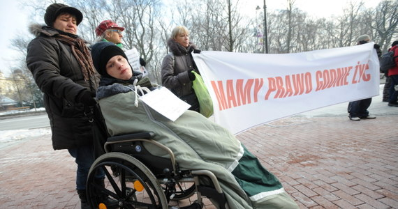 """""""Też mamy prawo do godnego życia"""" - mówili protestujący przed kancelarią premiera rodzice niepełnosprawnych dzieci. Chcą, by czas, który poświęcają na opiekowanie się chorymi dziećmi został im zaliczony na poczet przyszłej emerytury."""