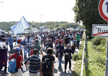 Setki uchodźców maszerują autostradą z Budapesztu do Wiednia. Niosą zdjęcia Merkel