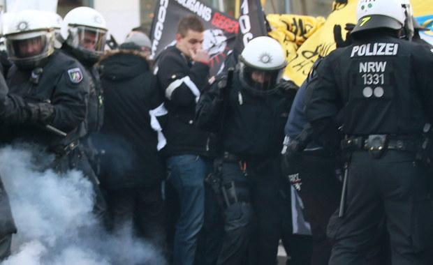"""Niespokojnie w niemieckiej Kolonii. Policja użyła armatek wodnych, by rozproszyć demonstrację zorganizowaną przez antyimigrancki, wrogi wobec islamu ruch społeczny Pegida. Wcześniej - według świadków, cytowanych przez Reutera - manifestanci zaczęli rzucać w kierunku policjantów petardami i butelkami z piwem. W starciach ranne zostały dwie osoby. Demonstracja została zorganizowana w reakcji na wydarzenia nocy sylwestrowej, kiedy w Kolonii doszło do wielu napaści seksualnych i rabunkowych na kobiety. Hasłem marszu było zawołanie: """"Pegida chroni"""". Inną manifestację zwołali przeciwnicy wykorzystywania wydarzeń w Kolonii do """"rasistowskiej nagonki"""" na imigrantów. Do zabezpieczenia miasta zaangażowanych zostało 1700 policjantów."""
