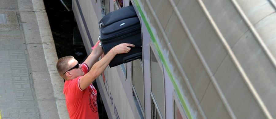 Trzech mężczyzn pomaga pasażerom i mieszkańcom przenosić ciężkie torby na drugą stronę kładki obok dworca w Grodzisku Mazowieckim. To alternatywa dla często psujących się wind. Władze miasta zaś cieszą się, że aktywizuje ona bezrobotnych.