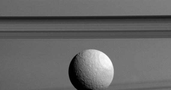 NASA opublikowała niezwykłe zdjęcie Tetydy, na którym wydaje się, że ten księżyc Saturna unosi się między... dwiema płaszczyznami pierścieni otaczających macierzystą planetę. Oczywiście pierścienie leżą w jednej płaszczyźnie i są widoczne powyżej Tetydy. To co widać poniżej księżyca to... cień pierścieni na powierzchni samego Saturna.