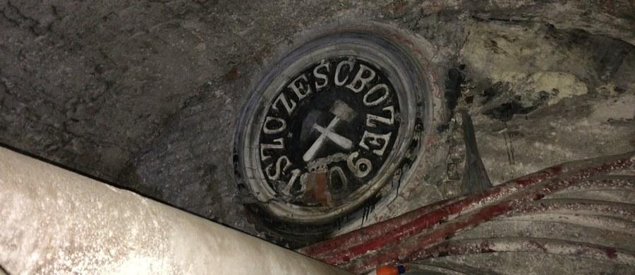 """Kopalnia Kazimierz Juliusz w Sosnowcu już nie fedruje, ale wydobyte zostaną z niej jeszcze cenne zabytki. To płaskorzeźby przedstawiające orła białego z napisem """"Szczęść Boże"""", pochodzące sprzed II wojny światowej. Konserwator zabytków właśnie je zabezpiecza, by w jak najlepszym stanie trafiły na powierzchnię. Za kilka dni podziemna część kopalni zostanie już całkowicie zamknięta."""