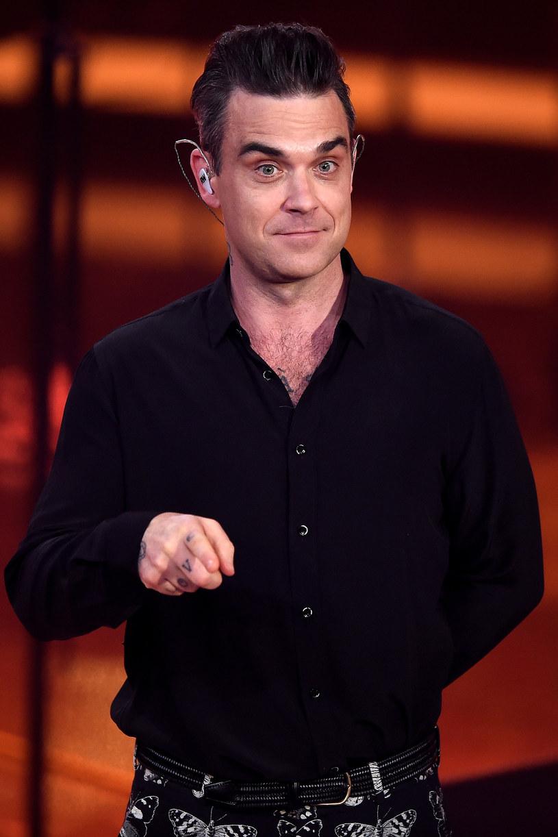 """Robbie Williams podczas nocy sylwestrowej zagrał koncert w Londynie. Kamera rejestrująca jego występ uchwyciła moment, w którym wokalista czyści ręce żelem antybakteryjnym po tym, jak przybijał """"piątki"""" z publicznością."""