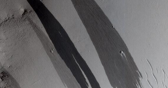 """Tajemnicze """"strumienie"""" na Marsie wcale nie muszą być śladami wody. Naukowcy z University of Paris-South kwestionują dotychczasowe teorie, tłumaczące dlaczego na stromych zboczach Czerwonej Planety pojawiają się ciemne, jakby wilgotne smugi. Jak pisze na swej stronie internetowej czasopismo """"New Scientist"""", nowa hipoteza wskazuje na to, że to po prostu lawiny piachu."""
