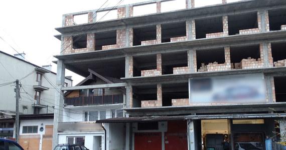 """Aż nie chce się wierzyć, że taki budynek naprawdę istnieje! Przy ulicy Centralnej 57, niedaleko ZIKiT-u w Krakowie powstało prawdziwe architektoniczne """"cudo""""! Dom jednorodzinny, obok warsztat samochodowy, a nad nimi niedokończony blok. To samowola budowlana. Urząd nakazał rozbiórkę nietypowej budowli, jednak inwestor od prawie roku nie reaguje na pisma urzędników."""