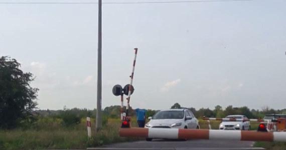 """Policja w Radomiu opublikowała nagranie, jakie otrzymała od jednej z internautek. Na filmie widać kierowcę, który podnosi szlaban i umożliwia innym wjechanie na przejazd kolejowy, tuz przed pociągiem. """"To skracanie sobie drogi do śmierci"""" - podkreślają policjanci i kolejarze. Kierowcy, którzy złamali przepisy zostali już ustaleni. Jednocześnie PKP Polskie Linie Kolejowe będą domagały pokrycia kosztów naprawy rogatki od mężczyzny, który tego dokonał."""