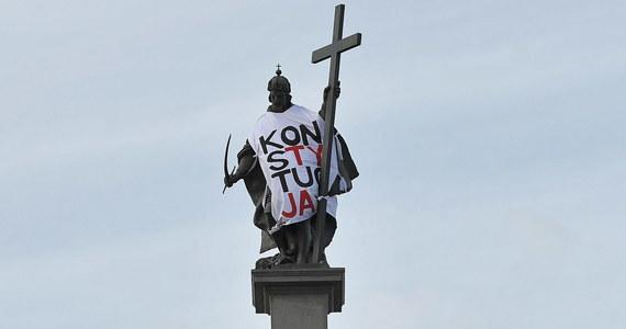 """Figura króla Zygmunta III Wazy stojąca na kolumnie na Placu Zamkowym została ubrana w koszulkę z napisem """"Konstytucja"""" przez uczestników demonstracji zorganizowanej przez Komitet Obrony Demokracji. Demonstranci około godziny 15:00 zebrali się na pl. Powstańców Warszawy skąd przeszli na Plac Zamkowy. Tam za pomocą wysięgnika, na figurę króla założyli koszulkę z napisem """"Konstytucja"""". W marszu uczestniczyło kilkaset osób, którzy mieli ze sobą flagi Polski, Unii Europejskiej i z logo KOD. Część protestujących trzymała egzemplarze Konstytucji RP."""