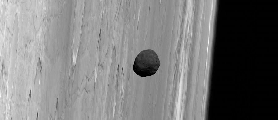 """Spór o pochodzenie księżyców Marsa rozpala astronomów od dawna. Konkurują ze sobą dwie teorie. Według pierwszej Fobos i Deimos mogą być przechwyconymi planetoidami, według drugiej, powstały z materiału wyrzuconego na orbitę Marsa po jego kolizji z innym masywnym obiektem. Najnowsza praca, opublikowana na łamach czasopisma """"Journal of Geophysical Research"""" przez badaczy ze Stony Brook University sugeruje, że ta druga teoria jest bardziej prawdopodobna, przynajmniej w przypadku Fobosa. Co ciekawe, praca  opiera się na nowej analizie danych zebranych... 20 lat temu."""