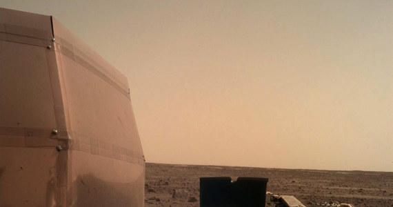 """Sonda InSight """"odpoczywa"""" na powierzchni Marsa po męczącej podróży i emocjonującym lądowaniu. Najnowsze laboratorium naukowe na Czerwonej Planecie rozłożyło już swoje baterie słoneczne, przesłało też pierwsze zdjęcie z kamery IDC (Instrument Deployment Camera). Obraz wykonany przez obiektyw przesłonięty jeszcze przezroczystą, przeciwpyłową osłoną przesłano za pośrednictwem krążącej na orbicie sondy Mars Odyssey."""