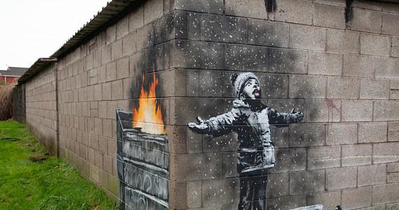 Ikona street artu Banksy pokazał na Instagramie swoje najnowsze dzieło - graffiti na jednym z garaży w walijskim Port Talbot, sercu brytyjskiego przemysłu stalowego. Pojawiły się już interpretacje, że to komentarz artysty do problemu zanieczyszczenia powietrza. Na ceglanej, pomalowanej na biało ścianie garażu widać chłopca z sankami, który podnosi twarz do góry i na wyciągnięty język próbuje złapać lecące z nieba płatki śniegu. Gdy jednak zmienimy perspektywę i przeniesiemy się za róg budynku, na sąsiedniej ścianie zobaczymy, że unoszące się w powietrzu drobiny to resztki odpadów z palącego się śmietnika.
