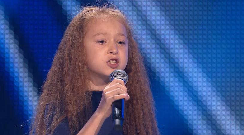 """Rude włosy, piegowata buzia i zawadiacki uśmiech - tak najłatwiej opisać dziewięcioletnią Nikolę Smutek, którą widzowie będą mogli zobaczyć w """"The Voice Kids""""."""