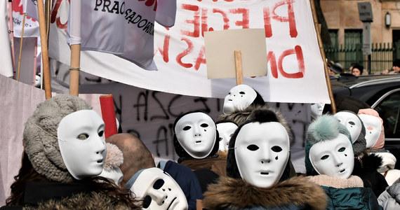 """Kilka tysięcy pracowników sądów i prokuratur manifestuje na ulicach Warszawy, domagając się podwyżek płac: w tym roku jeszcze o 450 złotych na rękę. Na transparentach widać hasła jak """"Dość pracy za grosze"""" czy """"Nie jesteśmy niewidzialni"""", a na twarzach protestujących… teatralne, płaczące maski. To - jak mówią pracownicy sądów i prokuratur - ironiczny komentarz do ich sytuacji."""