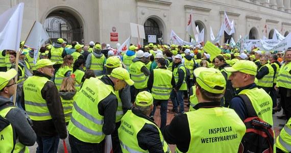 """""""Łagodzimy protest, ale nie kończymy go"""" - ogłosili pracownicy Inspekcji Weterynaryjnej. Dziś mieli blokować ważne drogi w 6 miastach, ale po rozmowach w ministerstwie rolnictwa zdecydowali inaczej."""