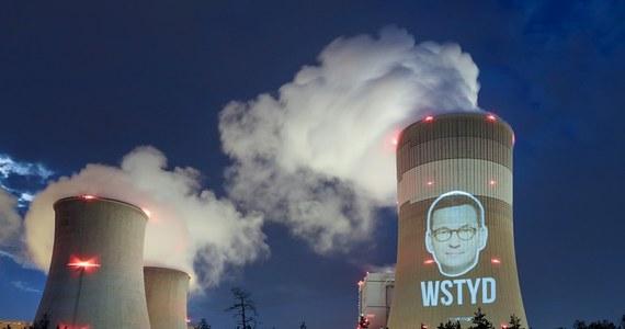 """Aktywiści Greenpeace wyświetlili na chłodni kominowej elektrowni w Bełchatowie twarz premiera Mateusza Morawieckiego oraz napis """"Wstyd"""". Zaprotestowali w ten sposób przeciwko zablokowaniu zapisu o dojściu UE do neutralności klimatycznej  do 2050 r."""