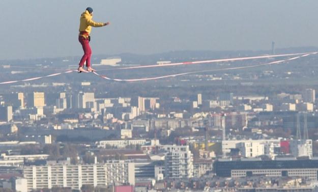Usytuowany na 150 m nad ziemią mężczyzna przeciwstawia się grawitacji, aby zachować równowagę na drucie rozciągniętym między dwoma wieżowcami.