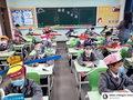 Dzieci w Chinach noszą czapeczki pomagające zachować dystans