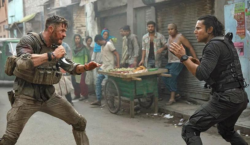 """Choć film """"Tyler Rake: Ocalenie"""" miał premierę niedawno, już cieszy się ogromną popularnością na całym świecie. Jego fani zastanawiają się nad tym, co stało się z tytułowym bohaterem granym przez Chrisa Hemswortha. Przeżył czy może zginął? Autorzy filmu wciąż trzymają ich w niepewności. Właśnie zamówiono scenariusz drugiej części tego filmu, który jest na dobrej drodze do tego, by zostać najpopularniejszą produkcją Netfliksa. Wciąż jednak nie rozwiewa to wszystkich wątpliwości."""