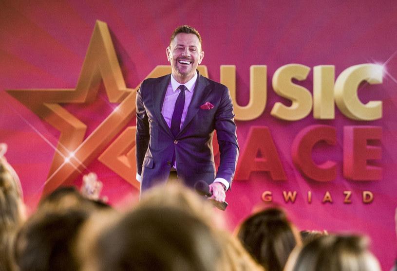 """W filmie """"Jak zostać gwiazdą"""" Krzysztof Ibisz wcielił się w prowadzącego talent show """"Music Race""""."""