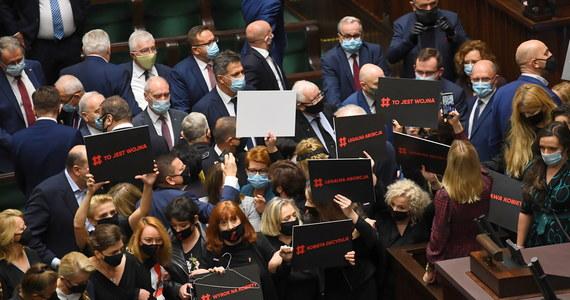 """Awantura w Sejmie - tak rozpoczęło się posiedzenie izby niższej parlamentu. Atmosfera była wyjątkowo napięta ze względu na ostatnie protesty przeciwko decyzji Trybunału Konstytucyjnego dotyczącej aborcji. Wicemarszałek Sejmu Ryszard Terlecki odnosząc się do błyskawicy, która jest jednym z symboli Strajku Kobiet, porównywał ją do emblematów Hitlerjugend i SS. Parlamentarzyści zaczęli się przepychać. Posłanki ugrupowań opozycyjnych zablokowały mównicę. Każda z nich miała ze sobą czarną tabliczkę z czerwonym napisem """"Kobieta decyduje"""". Straż Marszałkowska musiała podjąć interwencję."""