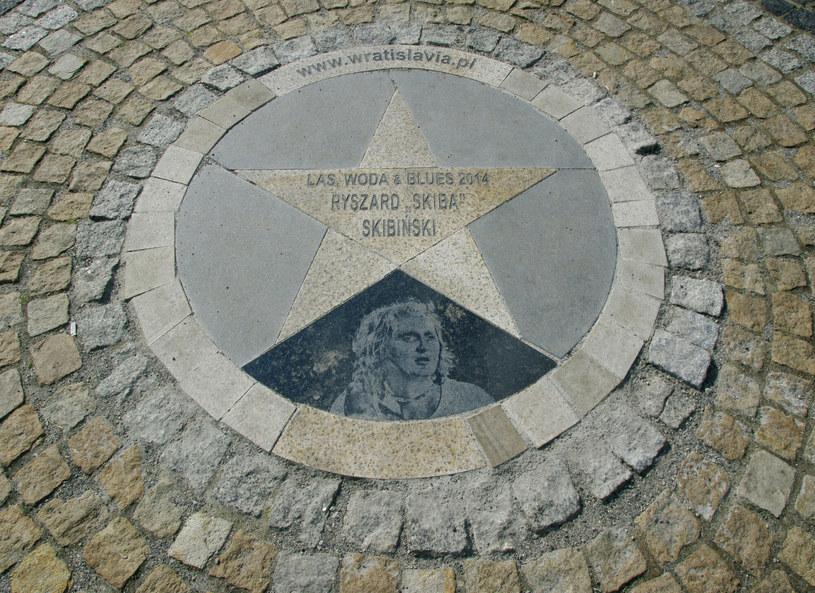 """Od czwartku skwer przy Białostockim Ośrodku Kultury nosi imię związanego z Białymstokiem muzyka, wirtuoza ustnej harmonijki Ryszarda """"Skiby"""" Skibińskiego. Jak podkreślano podczas uroczystości nadania imienia, muzyk jest zasłużoną postacią dla miasta i muzyki."""