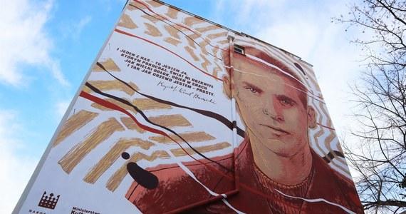 """W setną rocznicę urodzin Krzysztofa Kamila Baczyńskiego na warszawskim Powiślu odsłonięto mural upamiętniający tego poetę. Wizerunkowi artysty towarzyszy fragment jego wiersza """"Spojrzenie"""": """"I jeden z nas — to jestem ja, którym pokochał. Świat mi rozkwitł jak wielki obłok, ogień w snach i tak jak drzewo jestem — prosty""""."""