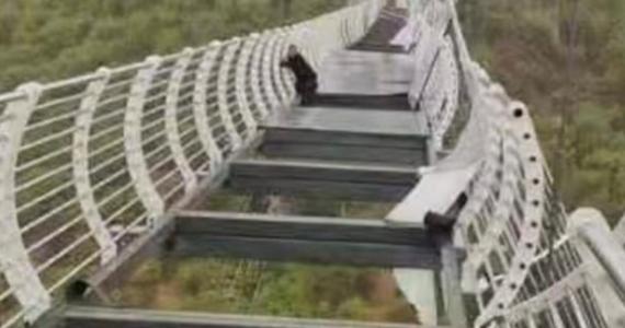 Na zdjęciu opublikowanym w przez oficjalną chińską agencję prasową Xinhua widać turystę kurczowo trzymającego się balustrady mostu, podczas gdy w naruszonej podłodze brakuje części dużych szklanych paneli.