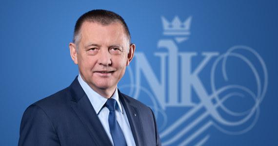 """W rozmowie z """"Dziennikiem Gazetą Prawną"""" prezes Najwyższej Izby Kontroli Marian Banaś ocenił, że to Mariusz Kamiński - szef resortu spraw wewnętrznych i administracji - """"rozdaje karty"""" i w jakimś sensie rządzi Polską. """"Wiem, że Kamiński zajmował się mną od 2018 r. On i różni funkcjonariusze, którzy są powiązani z układami mafijnymi, bo przecież nikt po 1990 r. porządnie tych służb nie zweryfikował"""" - zauważył. """"Myślę, że zbierane są haki na każdego, na wszelki wypadek"""" - dodał."""