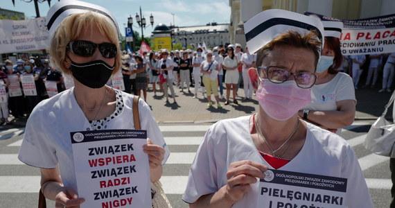 """Ok. 40 szpitali w całej Polsce brało dziś udział w strajku ostrzegawczym pielęgniarek i położnych. Jak przekazała przewodnicząca Ogólnopolskiego Związku Zawodowego Pielęgniarek i Położnych Krystyna Ptok, był to protest przeciwko warunkom pracy i płacy. """"Godna płaca za ciężką pracę"""" - to jedno z haseł, jakie można było usłyszeć w czasie protestu na placu Bankowym w Warszawie."""