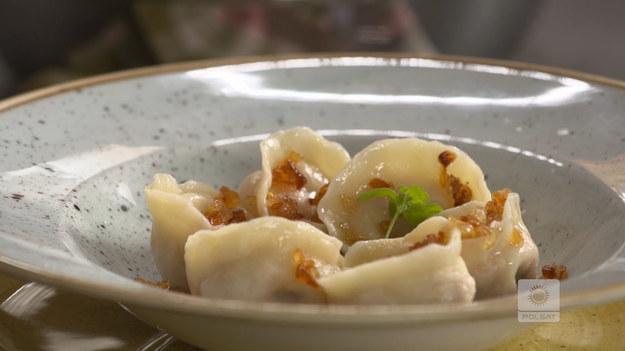 Mąkę zaparzyć gorącą wodą (wlać trochę i wymieszać nożem). Gdy zrobią się kluchy, wybić jajko. Posiekać, następnie wyrobić ciasto. Przykryć i odstawić na ok. 20 minut. Kiełbasę sparzyć we wrzątku. Gdy wystygnie, obrać z osłonki, pokroić na mniejsze kawałki, rozdrobnić widelcem i przełożyć do miski. Wybić jajko, przyprawić chrzanem, majerankiem, solą i świeżo zmielonym pieprzem. Wymieszać, przykryć i wstawić do lodówki. Ciasto rozwałkować, podsypując mąką. Za pomocą szklanki lub pierścienia wyciąć krążki. Na środku każdego położyć trochę farszu i zlepić brzegi (można zrobić uszka). Ugotować w osolonym wrzątku (po wypłynięciu wystarczy minuta). Zahartować w zimnej wodzie, odcedzić na sicie. Podawać ze zrumienioną na maśle cebulką. Udekorować świeżym majerankiem. SKŁADNIKI •½ kg - mąki •100 ml - ciepłej wody •1 - jajko DO PODANIA •smażona cebula •majeranek świeży FARSZ •1 kg - białej surowej kiełbasy •1 łyżka - chrzanu •1 - jajko •sól •pieprz •majeranek suszony