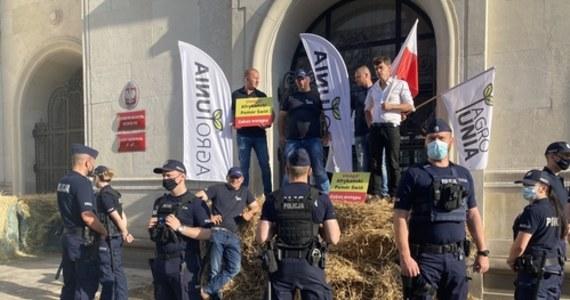 """Bele siana, rozlana gnojówka i odpalone race - tak wyglądał protest AGROunii przed gmachem resortu rolnictwa w Warszawie. Jego uczestnicy zamocowali na drzwiach gmachu łańcuchy i kłódki, którym towarzyszyły tabliczki z napisem: """"Afrykański Pomór Świń. Zakaz wstępu"""". """"Nie ma przyzwolenia na to, żeby ministerstwo, które nie działa, mogło być otwarte"""" - tłumaczył lider AGROunii Michał Kołodziejczak. """"Oni zamknęli się na nas. Dzisiaj my ich zamykamy w tym gmachu"""" - dodał."""