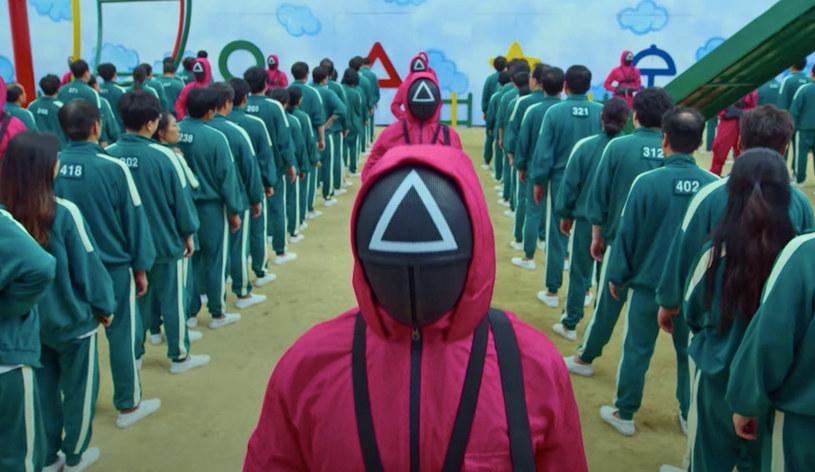 """""""Formularz zgody. Klauzula pierwsza: Gracz nie może przerwać gry. Klauzula druga: Kto odmówi udziału, zostanie wyeliminowany. Klauzula trzecia: Grę można przerwać głosem większości"""". Te proste trzy zasady zaczynają rywalizację, która wciągnęła widzów na całym świecie. Południowokoreański serial """"Squid Game"""" właśnie został najpopularniejszą produkcją Netfliksa w historii. Również w Polsce od wielu dni jest numerem jeden na streamingowej platformie."""