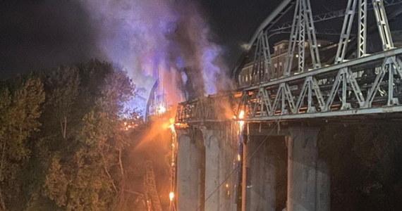 """W nocy most Ponte dell'Industria na Tybrze w Rzymie stanął w płomieniach. Strażakom udało się po kilku godzinach ugasić pożar, jednak konstrukcja budowli została poważnie uszkodzona. """"Serce się kraje, widząc kawałek historii, który staje się tym"""" - powiedziała burmistrz Rzymu, Virginia Raggi, która pojawiła się na miejscu."""