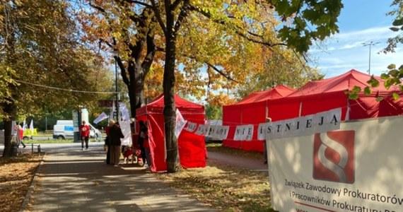 Kolejna odsłona protestu pracowników sądów w Czerwonym Miasteczku przed Ministerstwem Sprawiedliwości w Warszawie. Wiele jednostek w całej Polsce ze względu na braki kadrowe pracuje w ograniczonym zakresie, niektóre sądy odwołały wszystkie zaplanowane na dzisiaj rozprawy.