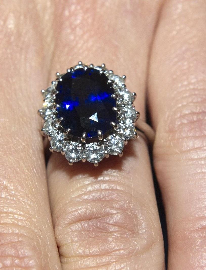 18-karatowy pierścionek z białego złota z owalnie szlifowanym 12-karatowym szafirem cejlońskim otoczonym 14 małymi brylantami. Ciąży na nim klątwa? /East News