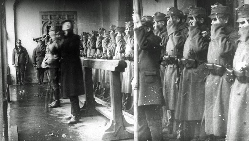 31 października 1918 r. Żołnierze pierwszej polskiej warty na odwachu krakowskiego ratusza składają przysięgę. Do czapek przypięte biało-czerwone kokardy. /Z archiwum Narodowego Archiwum Cyfrowego