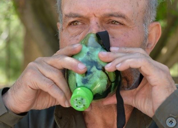 74-letni emerytowany oficer Abu Tarek pokazuje zrobioną przez siebie maskę przeciwgazową /AFP