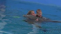 8-latek bez nóg pływa z delfinem z protezą ogona