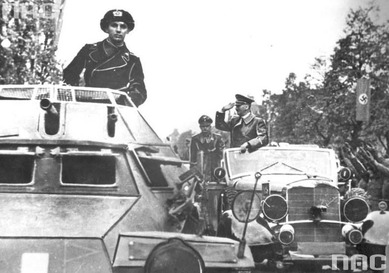 Adolf Hitler w Warszawie pozdrawia z samochodu mercedes salutujących żołnierzy. Na pierwszym planie wóz pancerny SdKfz 222 /Z archiwum Narodowego Archiwum Cyfrowego