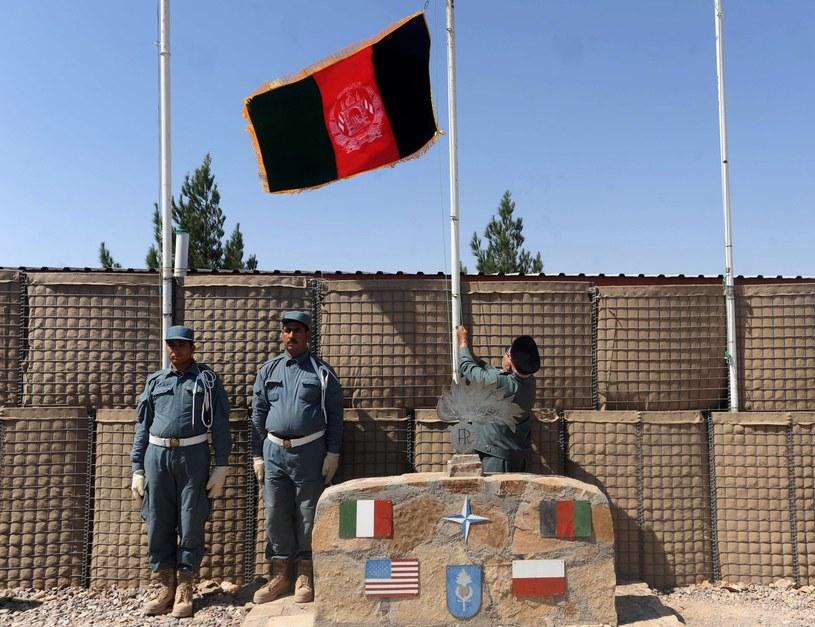 Afgańscy policjanci po wciągnięciu flagi swojego państwa na maszt centrum szkoleniowego w Heracie /AFP